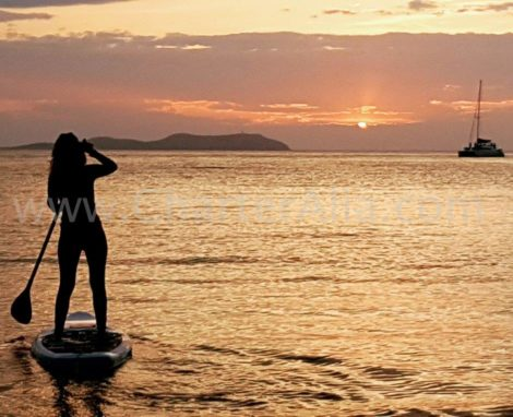 Paddle Surfen in den Sonnenuntergang waehrend des Katamarans Vermietung mit Uebernachtung