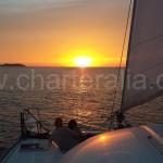 catamaran sailing towards the sunset in ibiza