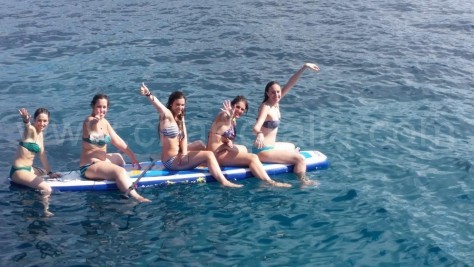 five people on the stand up paddle suft at cala conta ibiza
