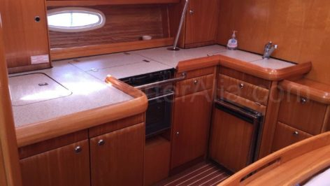 Interior living room with integrated kitchen in the sailing ship Bavaria 46