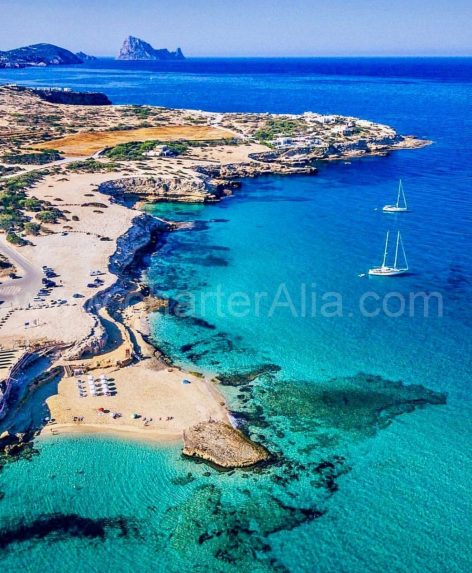 Aerial view of Cala Comte with sailboat for hire in Ibiza anchored at shore