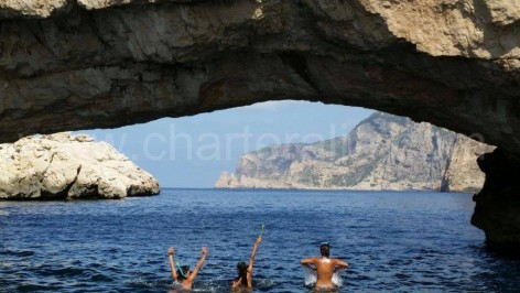 Girls swimming under the bow of Ses Margarides in Ibiza