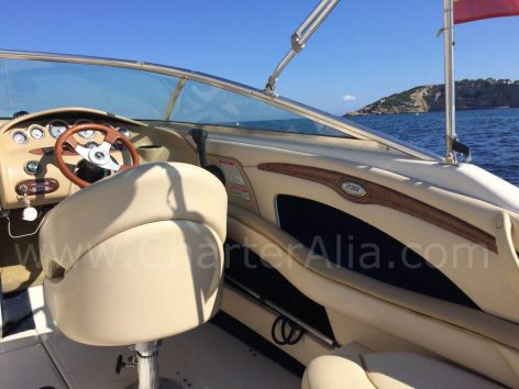 Helm of Sea Ray 230 speedboat chartering in Ibiza for full day excursion
