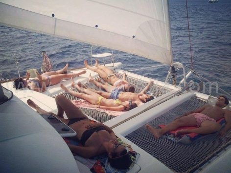 Clients laying down on the nylon trampolines on a catamaran charter in Ibiza Lagoon 380 2018