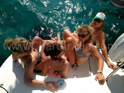 Clients sitting on swimming platform of catamaran for charter in Ibiza