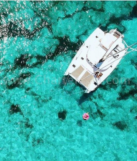Drone view of 2019 Lagoon 380 catamaran anchored in Formentera and the clients enjoying