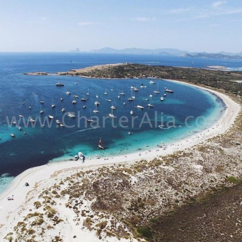 The southern bay of Espalmador full of charter boats in Formentera