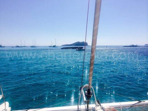bright sea sailing towards Ibiza forest island