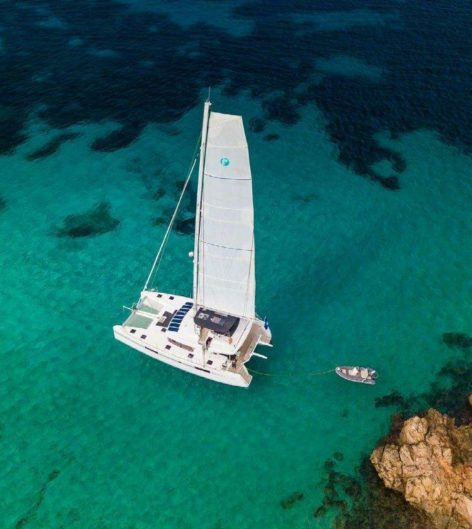 Drone view of the Lagoon 52 mega catamaran sailing off the coast of Ibiza Island
