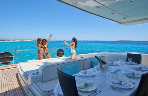Spacious dinner table with shade on the rental yacht in Ibiza Mangusta 130