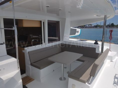 The Lagoon 400 catamaran aft deck has an exterior dining table with capacity up to 8 people