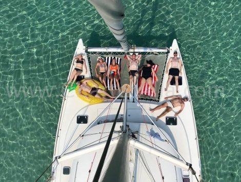 Vue du ciel du catamaran Lagoon 380 depuis le mat avec les clients allonges sur les trampolines