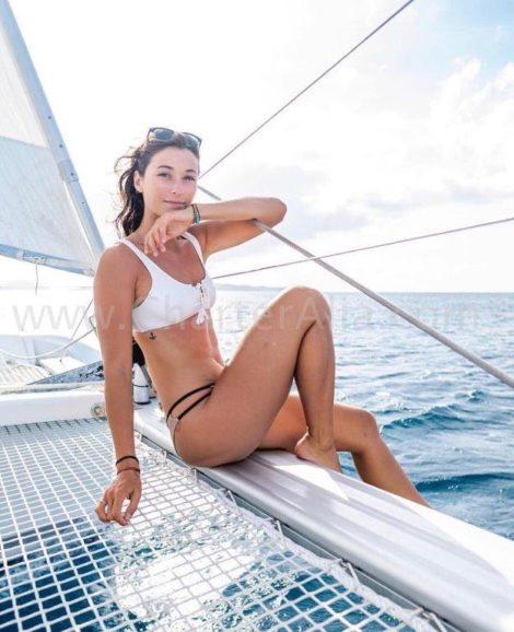 Ragazza in bikini che naviga su una trave in un catamarano Lagoon 380 di CharterAlia a Ibiza