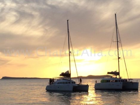 Il Lagoon 380 vicino al Lagoon 400 naviga parallelamente al tramonto. Uno dei prodotti piu popolari nella zona di San Antonio e Cafe del Mar