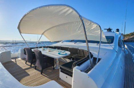 Ponte superiore ombreggiato sul noleggio di 130 mega yacht Mangusta a Ibiza