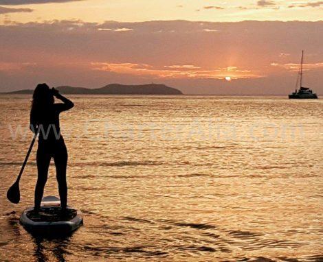 Paddle surfen op de zonsondergang tijdens catamaranverhuur met overnachting