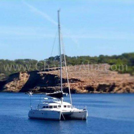Catamaran Lagoon 380 2018 verankerd aan het strand van Cala Bassa op Ibiza
