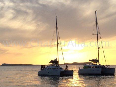 Lagoon 380 in combo waarbij de lagoon 400 parallel vaart tijdens de zonsondergang