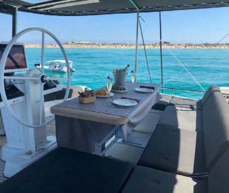 Het bovendek van de Lagoon 52 catamaran met het roer heeft ook een tafel