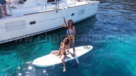 Menina no paddleboard ao lado do catamarã em Ibiza