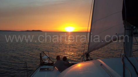 катамаран плывущии к закату на Ибице