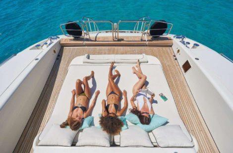 Наслаждаясь шезлонгами нижней задней палубы Mangusta 130 на яхте в аренду на Ибице