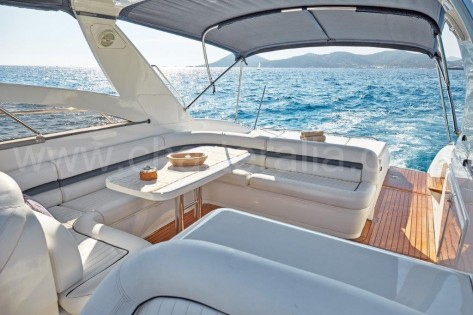 Suelo de teka y lujosos sofas de cuero blanco en embarcacion Princess V55 en Formentera