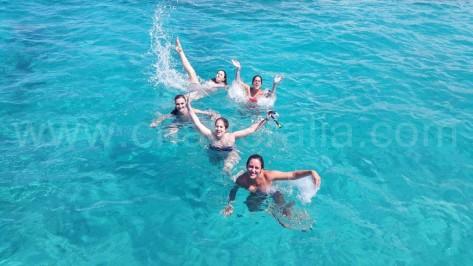 chicas en Ibiza nadando hacia el barco de alquiler