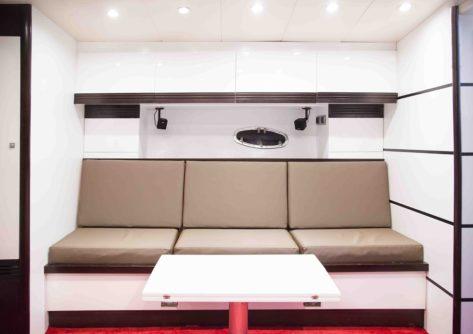 Comodo salon con mesa retractil dentro del yate Stealth 50 en alquiler en Ibiza y Formentera