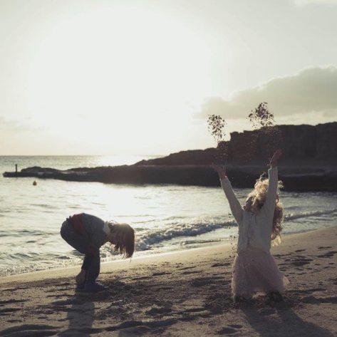 Niños disfrutando con la arena de Cala Tarida