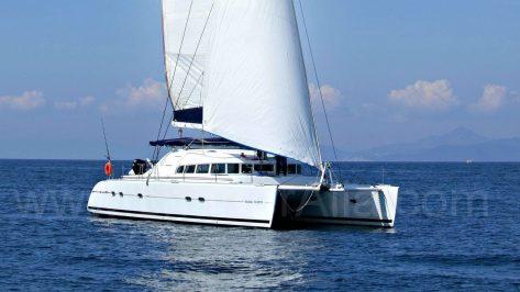 Vista lateral del catamarán Lagoon 470 disponible para alquilar en las Islas Baleares