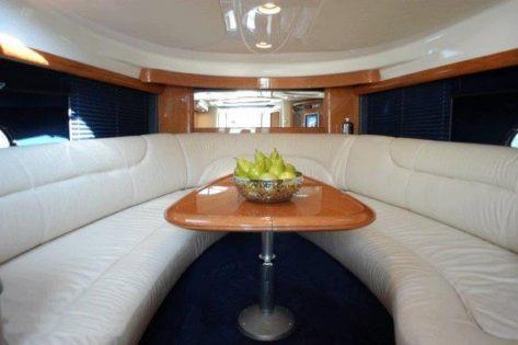mesa y sofas dentro del yate para alquilar en ibiza