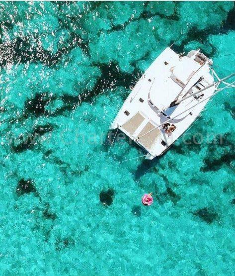 Foto a vista de drone del catamaran Lagoon 380 2019 fondeado en Formentera y los clientes disfrutando