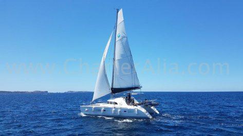 Imagen del catamaran de alquiler de Ibiza Lagoon 380 navegando a vela en la bahía de San Antonio