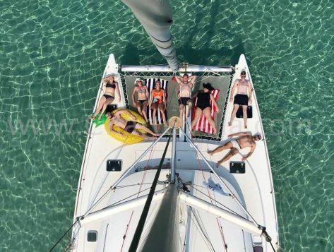 Vista cenital del catamaran Lagoon 380 desde tope de palo con clientes disfrutando de las redes de proa