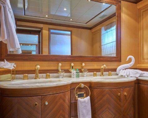 Bano con lavabo doble y ornamentos dorados en el Mangusta 130 para alquiler en Ibiza